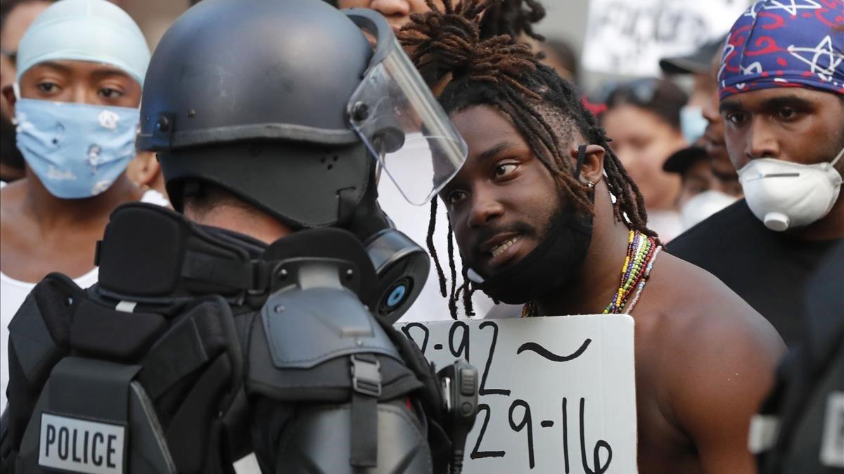 Los manifestantes se enfrentan a la policía con equipo antidisturbios en el centro de Raleigh N C.