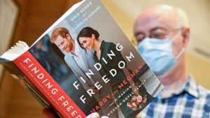 El empleado de una librería de Londres, con un ejemplar de 'Finding freedom' Encontrando la libertad.