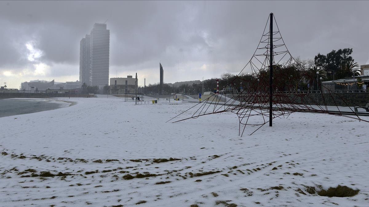 La playa de la Nova Icària se ha cubierto con un manto granulado de nieve, este mediodía.