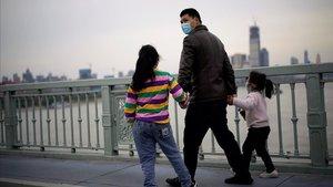 Un adulto y dos niños cruzan el puente deWuhan, capital deHubei, en China.