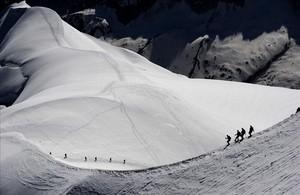 Alpinistas caminansobre el macizo del Mont-Blanc por encima de la Vallée Blanche en los Alpes franceses.