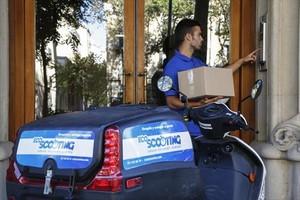 REPARTOUn trabajador de Ecoscooting entrega un paquete con su vehículo eléctrico.