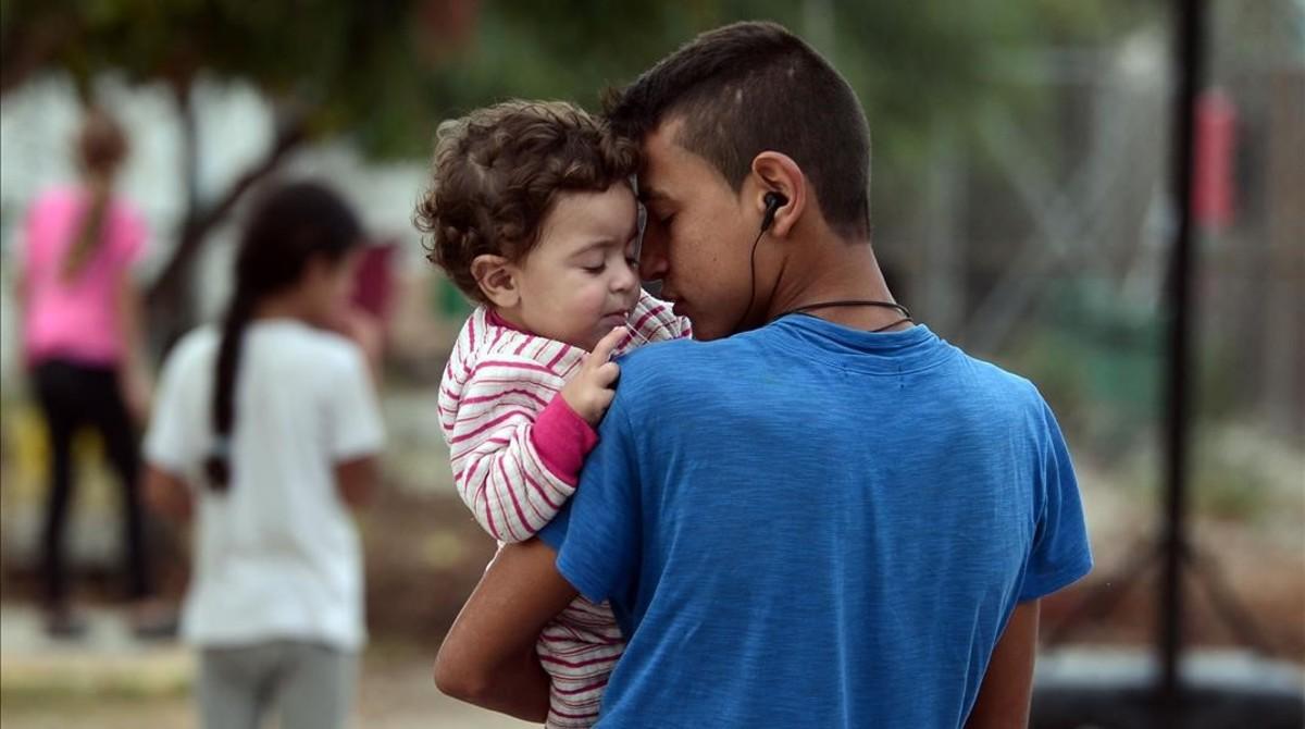 Un chico sostiene en brazos a su hermano pequeño en el campo de refugiados de Kara Tepe, donde algunos fueron trasladados tras un incendio en el de Moria, en Lesbos (Grecia), el 21 de septiembre.