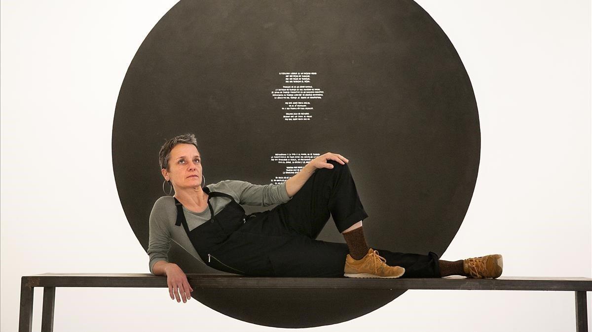 Christina Schultz, artista participante en la exposiciónPerder el tiempo y encima procurarse un reloj para este propósito, posa en actitud relajada frente a su obra.