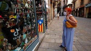 Una mujer con mascarilla observa una tienda de souvenirs en Barcelona.