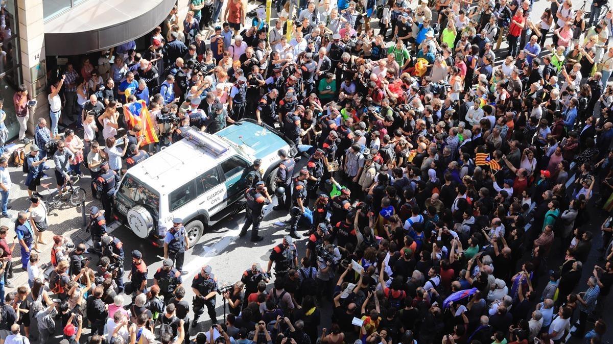 Decenas de personas intentan impedir que salga el coche de la Guardia Civil tras el registro al Departament d'Afers Exteriors de la Generalitat.