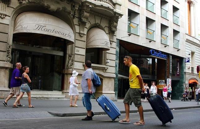 Dos turistas cruzan la Rambla cargados con maletas camino de su hotel.