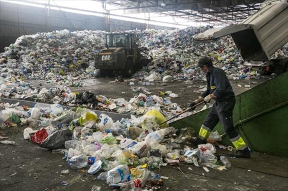 Un empleado trabaja con residuos en las instalaciones de la planta de tratamiento y selección de envases de Gavà, para su posterior reciclaje.