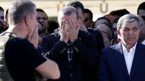 Erdogan reza junto al expresidente turco Abdulá Gul (derecha) en el funeral por los muertos en el golpe de Estado fallido.