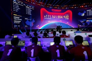 Empleados de Alibaba observan en una pantalla gigante el volumen de ventas de la empresa en elDía del Soltero.