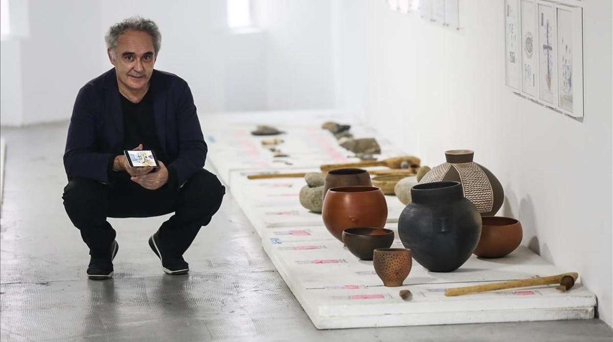 Ferran Adrià sostiene un móvil con la app Tu cuento en la cocina, junto a objetos de cocina del Neolítico, en el BulliLab.
