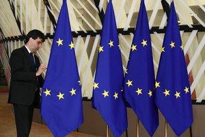 Un funcionario prepara las banderas de la Unión Europea antes del inicio de la cumbre, este domingo en Bruselas.