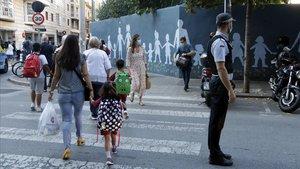 Un policía local regula el tráfico frente al acceso de la escuela Vedruna, en Girona.