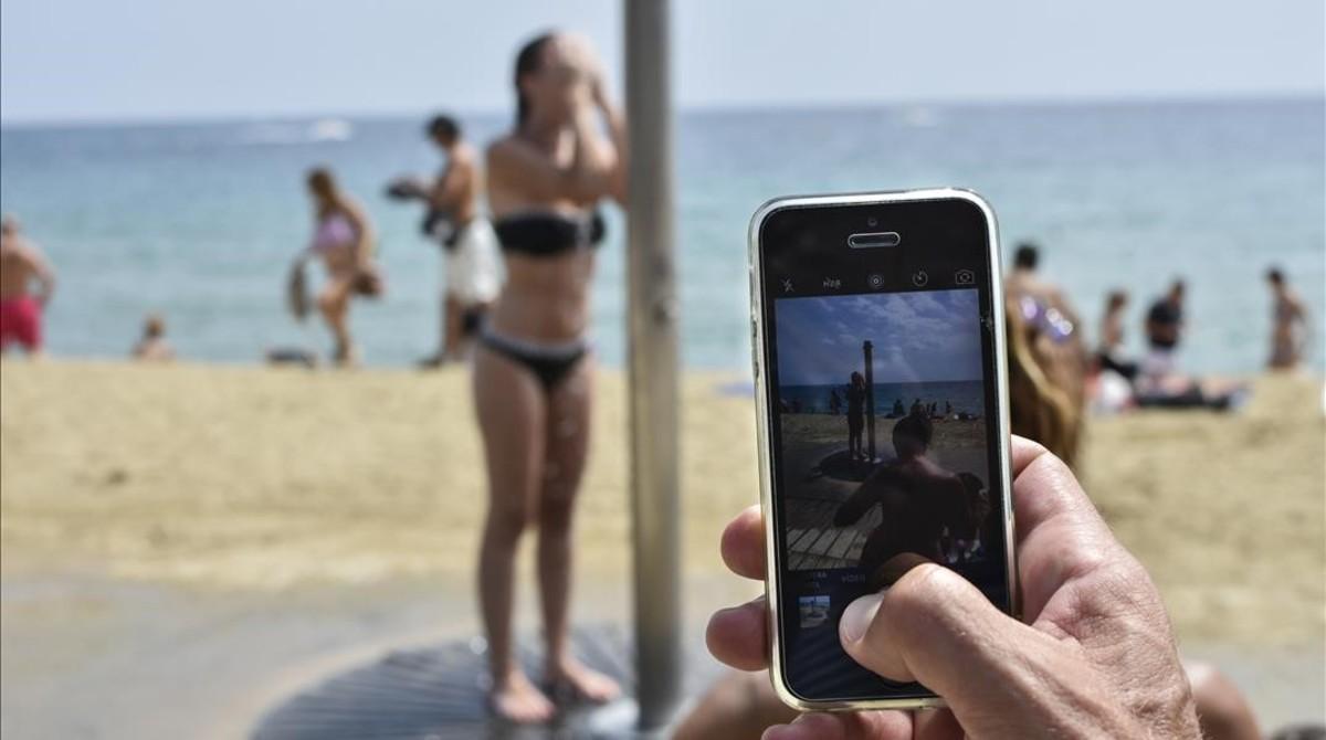 Una mujer se ducha en la playa de Barcelona delante de la cámara de un teléfono móvil.