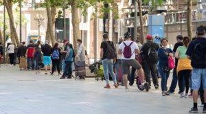 Larga cola de personas en situación del vulnerabilidad que esperan para recoger comida en la parroquia de Santa Anna de Barcelona, el pasado 18 de mayo.