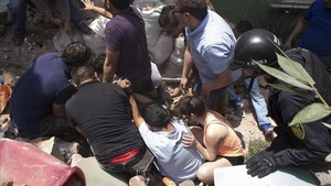 Los equipos de rescate sacan con vida a un hombre de entre los escombros.