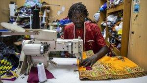 El costurero senegales Mor Mbaye en su tienda en el barrio de Russafa (València)