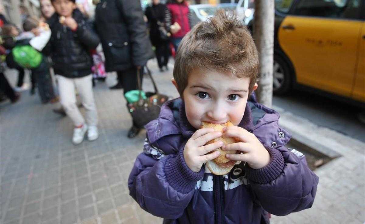 Un niño come un bocadillo a la salida del colegio.
