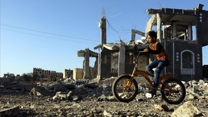 Un niño yemení pasea con su bicicleta junto a los escombros de una vivenda en Sanádestrozada por los bombardeos aéreos