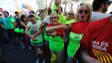 """Participantes ala manifestación se preparan con la camiseta de la """"Diada pel sí""""."""