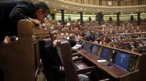 Patxi López y Eduardo Madina hablan ante la nueva butaca que ocupará Pedro Sánchez en el Congreso.
