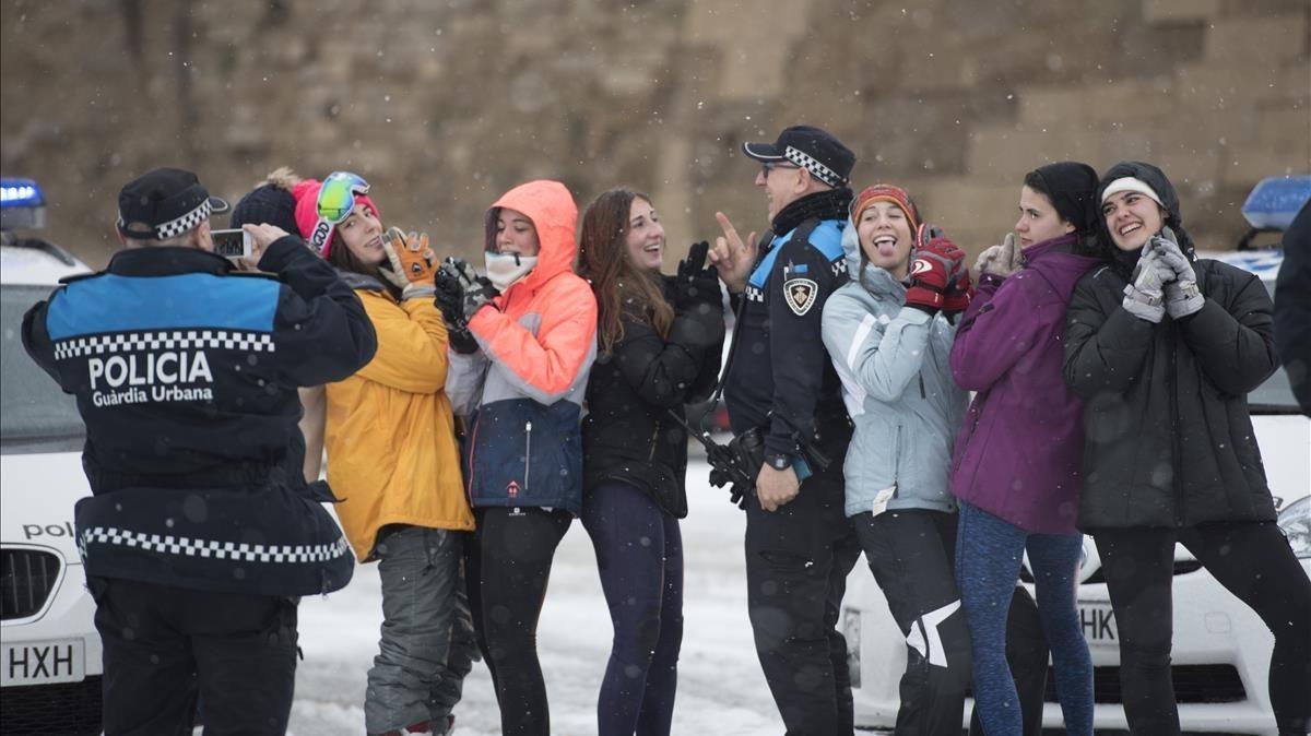 Un policía local fotografía a unos jóvenes tras la nevada.