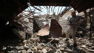 Un soldado de las Fuerzas de Movilización Popular comprueba los restos de la tumba del dictador iraquí SadamHusein en Ouja, al sur de la ciudad de Tikrit.