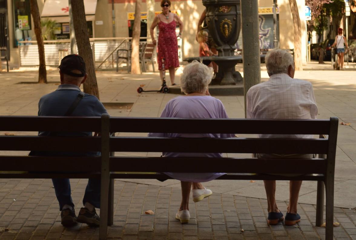 Tres pensionistas descansan en un banco en la plaza del surtidor de Poble Sec, en Barcelona.
