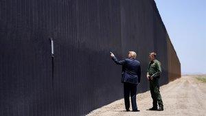 El presidenteTrump conversa con el jefe de la Patrulla de Fronteras, Rodney Scott., junto al muro que marca la frontera con México enSan Luis Ariz.