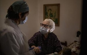Pepita Jové, de 92 años, junto a su cuidadora Laura Valdés, en su casa de Barcelona. Pepita vive sola en su casa y recibe alimentos de los servicios sociales tres veces al día.
