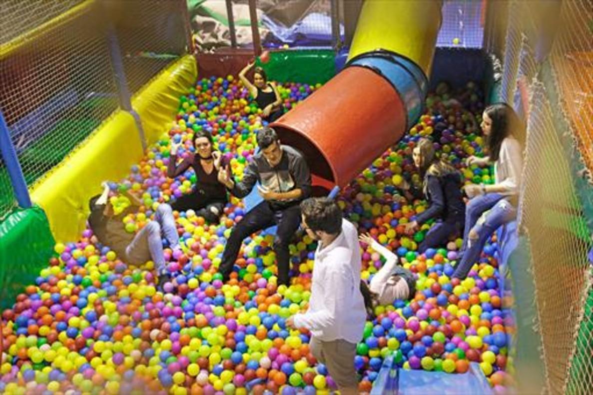 Un grupo de amigos celebran un cumpleaños (18 años) tirándose bolas en el parque infantil de Happy Parc Sants.