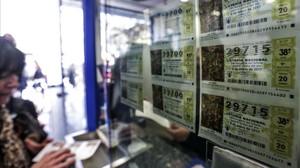 Una mujer compra varios décimos de El Niño, este miércoles, en una administración de lotería de València.