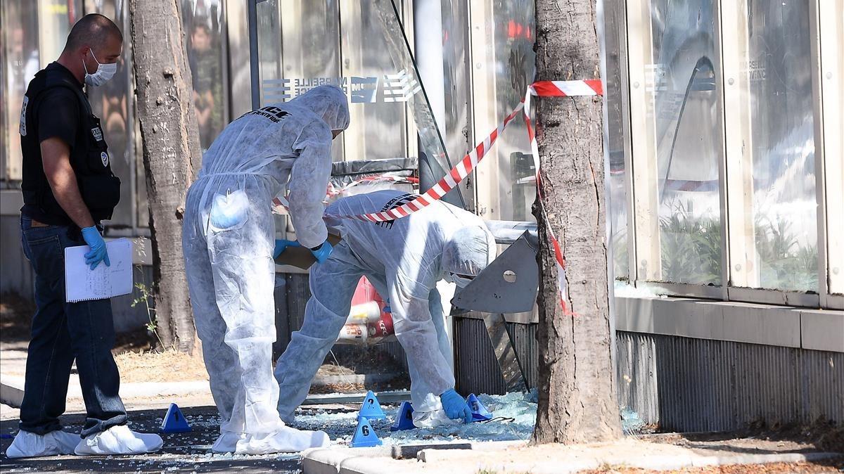 La policía francesa examina la zona después que un coche se haya estrellado en una parada de bus en Marsella (Francia).