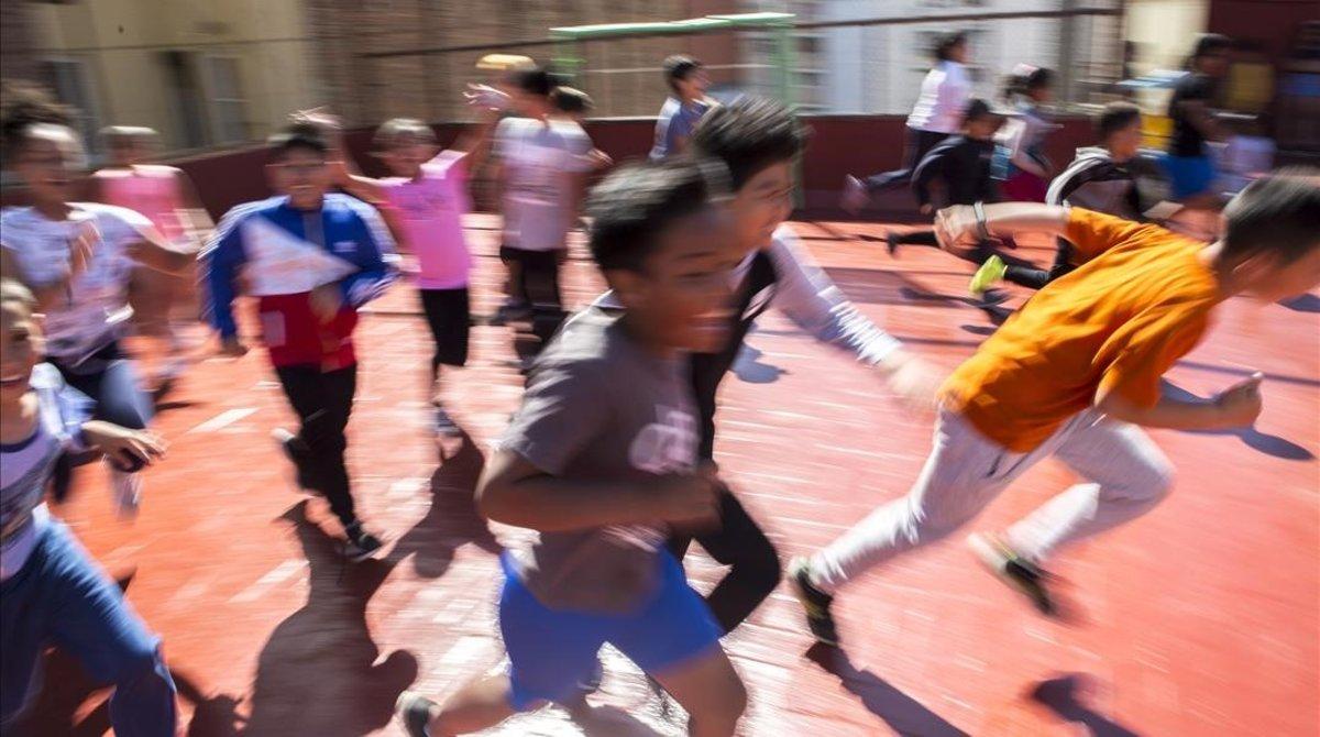 Niños en el patio de la escuela cooperativa a punto de cerrar.