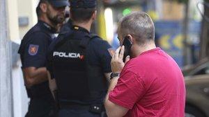 Un hombre habla por teléfono junto a tres policías, en Madrid.