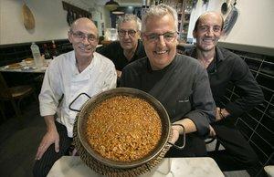 El dueño y chef de Can Boneta, JoanBoneta, muestra una paella acompañado de personal de su restaurante.