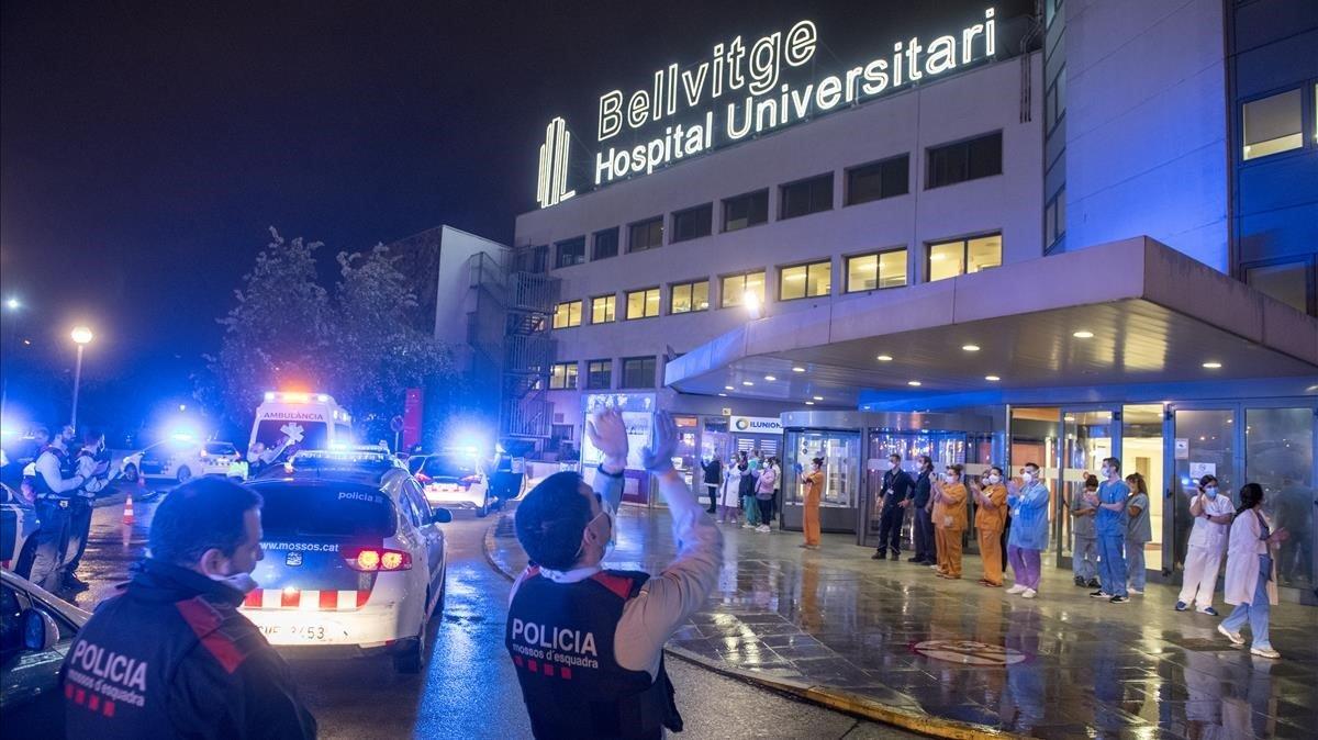 Agentes de los Mossos aplauden a los sanitarios en el hospital de Bellvitge.