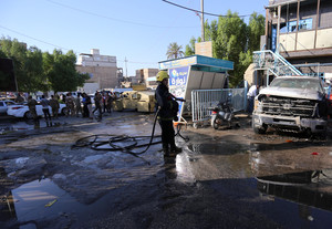 A firefighter hoses down a street after a suicide bomb attack in the city of Kerbala