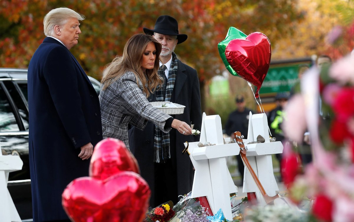 U S  President Donald Trump watches as first lady Melania Trump places a flower on a memorial to shooting victims as they stand with Tree of Life Synagogue Rabbi Jeffrey Myers outside the synagogue where a gunman killed and wounded people during a mass shooting in Pittsburgh  Pennsylvania  U S  REUTERS Kevin Lamarque