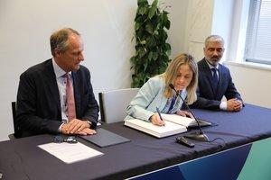 Emma Navarro, vicepresidenta del BEI, firma el acuerdo de financiación de Almirall, ante la atenta mirada del consejero delegado de la compañía, Peter Guenter (izquierda), y Bhushan Hardas, responsable científico de la farmacéutica.