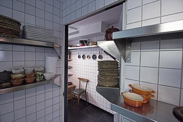 El acceso a El cuarto frío se hace por una puerta alicatada y con estanterías.
