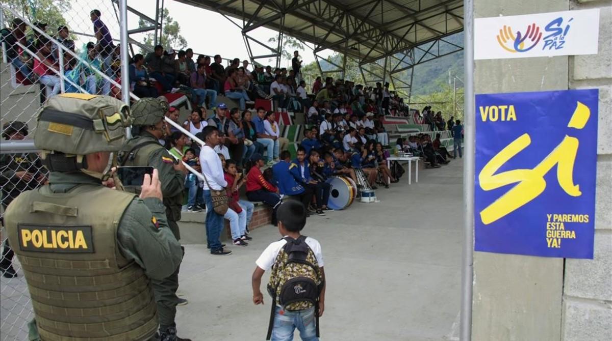Un agente de policía fotografía un acto a favor del 'sí' en el plebiscito, en Toribío.