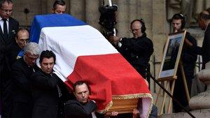 El ataúd del expresidente francés Jacques Chirac, cubierto con la bandera nacional francesa, es llevado por portadores a la salida de la iglesia de Saint-Sulpice, en París, este lunes.