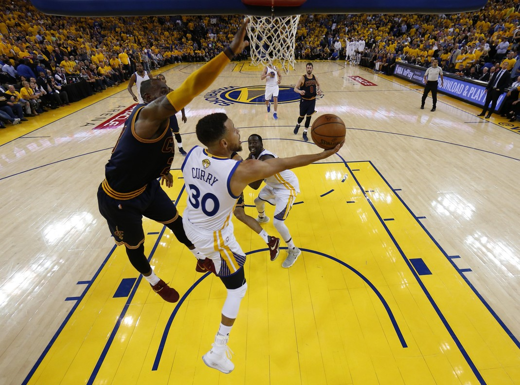 Curry y James pelean bajo el aro.