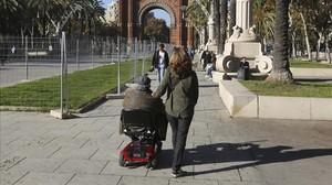Una mujer pasea junto a una una persona dependientepor el entorno del Arc de Triomf de Barcelona.