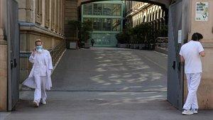 Dos trabajadores del Hospital Clínic de Barcelona, a las puertas del centro, este jueves.