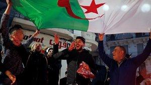 Un grupo de argelinos celebra en las calles de Argel la decisión de Buteflika de no volverse a presentar como candidato a la presidencia del país.