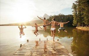 Un grupo de jóvenes saltando a un lago.