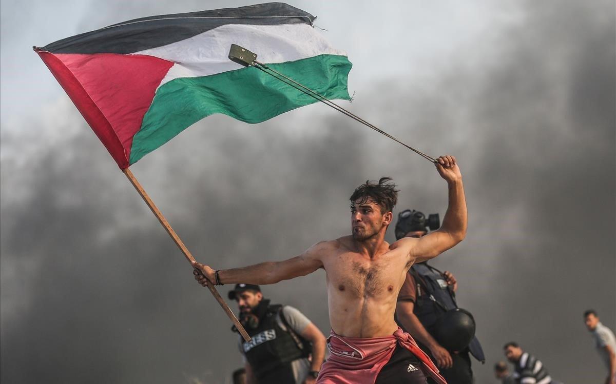 Un joven palestino tira piedras con una honda mientras con la otra mano lleva la bandera palestina.