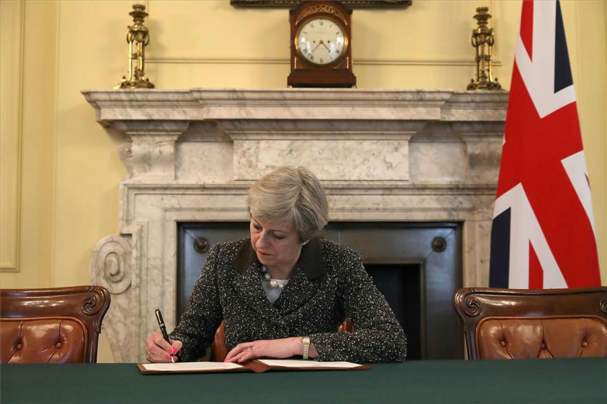 La primera ministra británica, Theresa May, firma la carta con la que arranca el brexit.